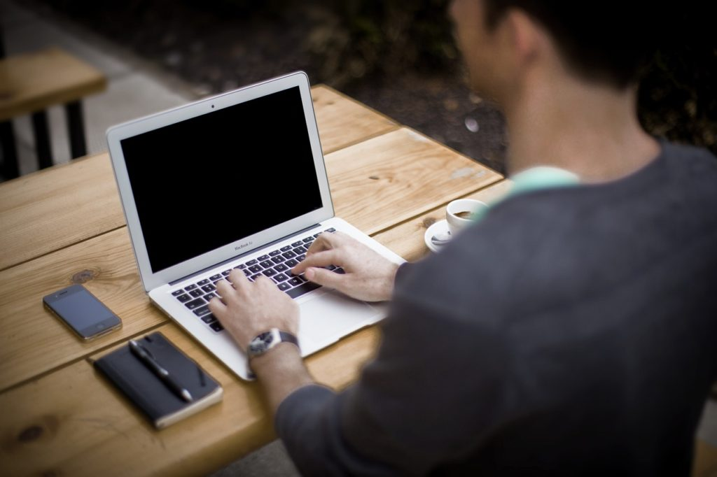 Guy using Macbook Air on the wooden table along with notebbok and iphone