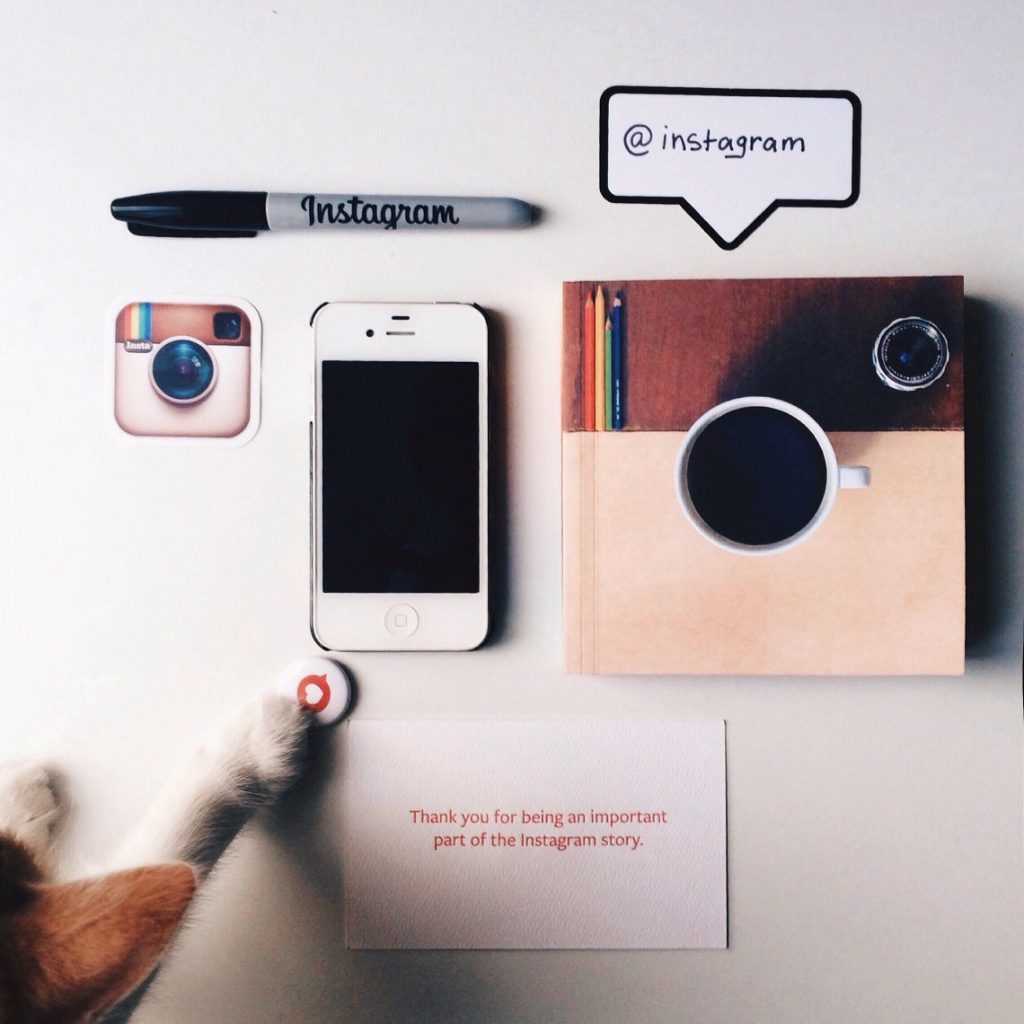 Cat paw along with iphone, instagram logo and notebook with coffee logo printed
